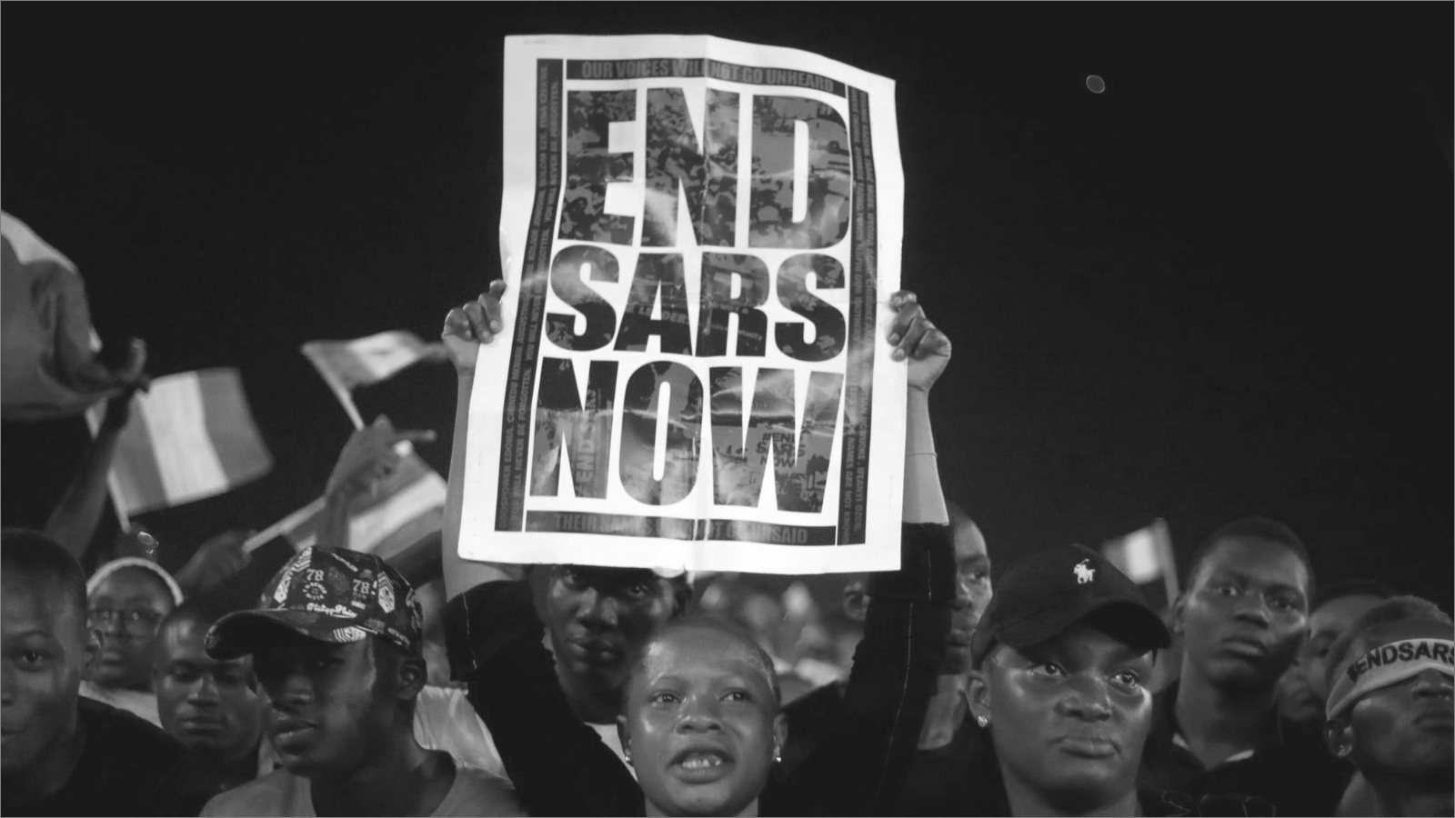 person holding End SARS now poster